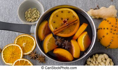pot with hot mulled wine, orange slices and spices -...