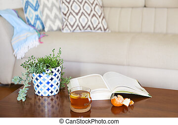 Pot with succulent plants and opened book with the tea on wooden table.