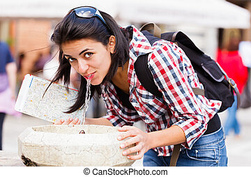 Beautiful tourist with map drinking clean, filtered fresh water from street fountain.