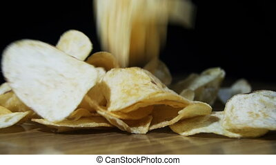 Potato Chips are Falling on a Wooden Table on Black Background in Slow Motion