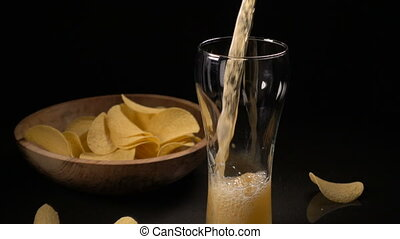 Potato chips are poured into a wooden bowl and beer is poured into a glass