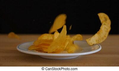 Potato chips falling into a plate
