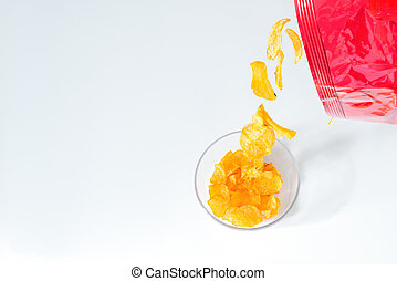 Potato chips falling out of a packet of crisps into a glass bowl on white couch table