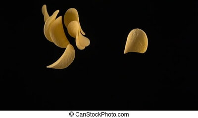 potato chips in free fall on a black background, slow motion