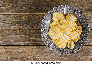 Potato chips in silver vintage plate on wooden background.