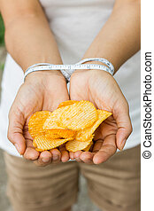 Potato chips in woman hand, tied with Measuring tape, concept st