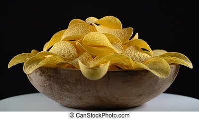 potato chips in wooden bowl rotating on a black background,...