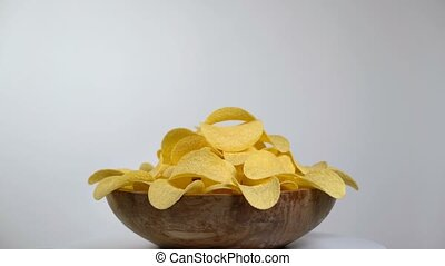 potato chips in wooden bowl rotating on a white background,...
