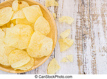 Potato chips in wooden plate on white wooden table