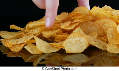 Potato chips lie on a mirror surface randomly scattered on a...