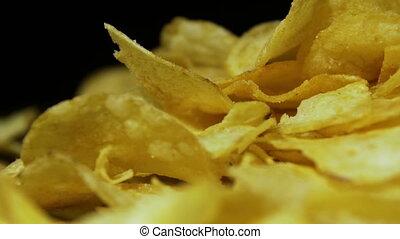 Potato Chips Rotating On Black Background. Potato chips are...