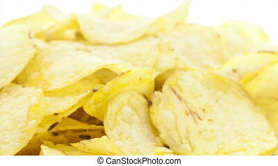 Potato chipsPotato chips rotating on the white table with...