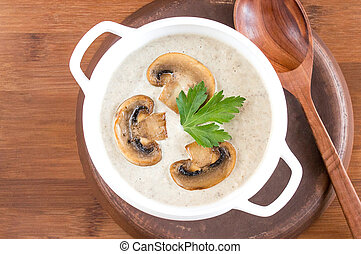 Potato cream soup with mushrooms. Wooden background, a large spoon.