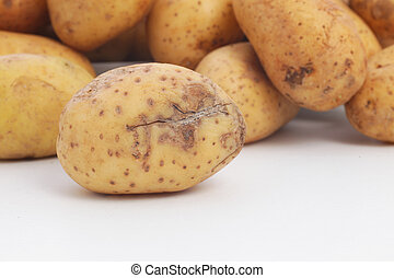 Fresh whole raw potato damaged during harvesting with a cut through the skin which is discolouring