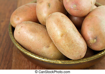 potato in dish on brown background