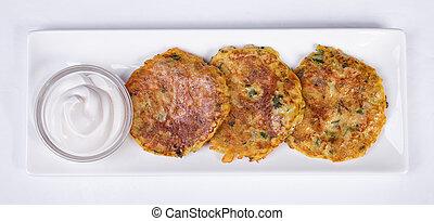 Potato Pancake with Sour Cream on a white background