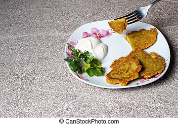 Potato pancakes on a plate, served with sour cream and parsley.