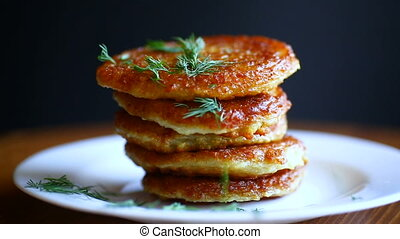 potato pancakes with dill in a plate on a wooden table