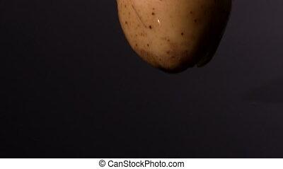 Potato pieces falling on wet black