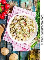 potato salad with fresh radishes in a white bowl on a rustic wooden table