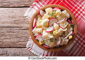 potato salad with radish and eggs in a bowl. horizontal top view