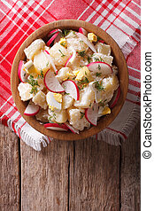 potato salad with radish and eggs in a bowl. Vertical top view