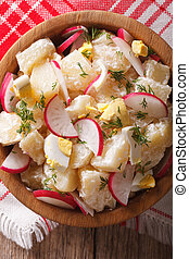 potato salad with radish close-up in a bowl. Vertical top view