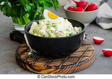 Potato salad with radish, eggs, green peas, sour cream and mayonnaise in a bowl on a board on a dark concrete background. Horizontal orientation, close up.