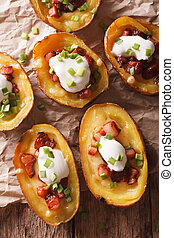 Potato skins with cheese and bacon close-up on the table. vertical top view