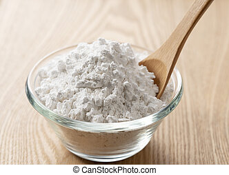 Potato starch and a wooden spoon on the table.