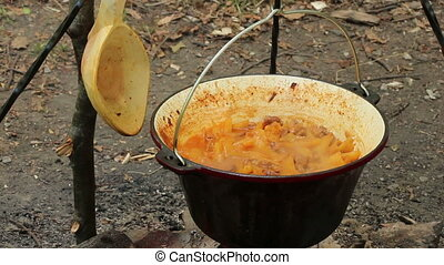 Potato stew in cauldron with wooden spoon by side