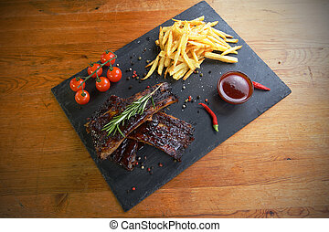 potatoes and pork ribs - fried potatoes and pork ribs on...