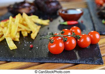 potatoes and pork - fried potatoes and pork with bone on...