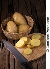 Potatoes and potato sliced on wooden table. Selective focus