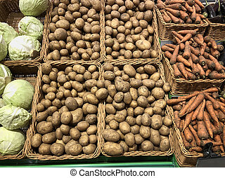 Potatoes, carrots and cabbage in a supermarket