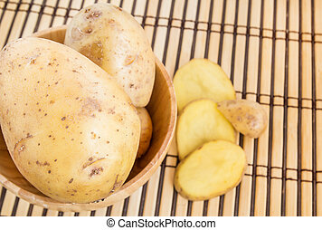 Potatoes in wooden bowl on a wooden background