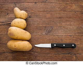 Potatoes on rustic board with knife. - Staple food.