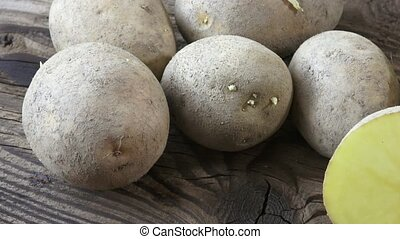 Potatoes on wooden background. Unpeeled dirty raw organic potatoes