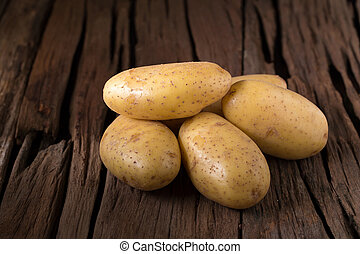 Potatoes on wooden table. Selective focus