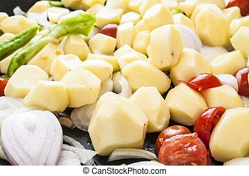 Potatoes tomatoes onion and peppers parties, ready to bake