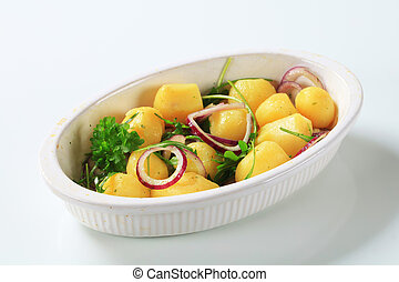 Potatoes with onion and arugula in casserole dish