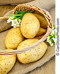 Potatoes yellow with flower in basket on sacking