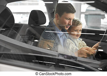 Potential buyer of car testing car with son.
