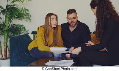 Potential buyers are looking at documents and discussing agreement conditions with housing agent while sitting on couch in new apartment. Relocation and purchase concept.
