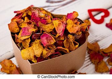 Potpourri and chestnuts in box. Heart near box with potpourri. Aroma of romance.
