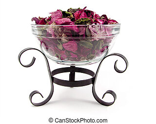 A picture of glass bowl full of potpourri kept on a stand. gives a very spa environment