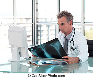 Middle aged doctor working at his Desk - Potrait of a Middle...