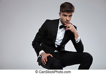 potrait of pensive young man in black tuxedo sitting