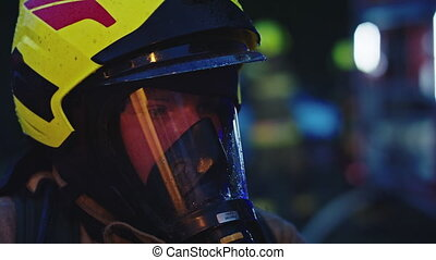 Potrait of young firefighter in full uniform in front of burning house