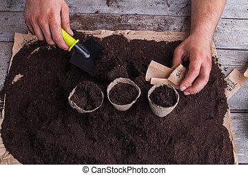 Pots planting process, gardener hands with trowel shovel.